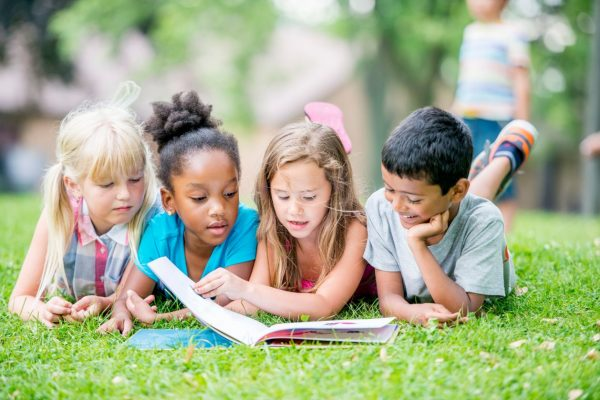 Three young girls and a boy are outdoors during summer. They are laying in the grass and reading a book together.