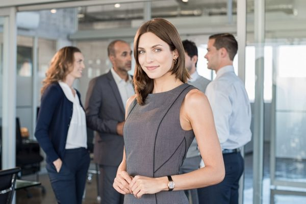 Successful formal woman standing in front of businesspeople and smiling. Portrait of confident and proud businesswoman with business team at modern office. Beautiful satisfied businesswoman looking at camera.