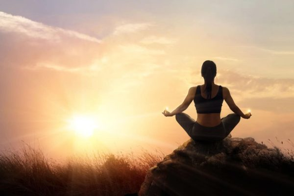 Woman practices meditating yoga at is an asana on a stone, sunset mountains background